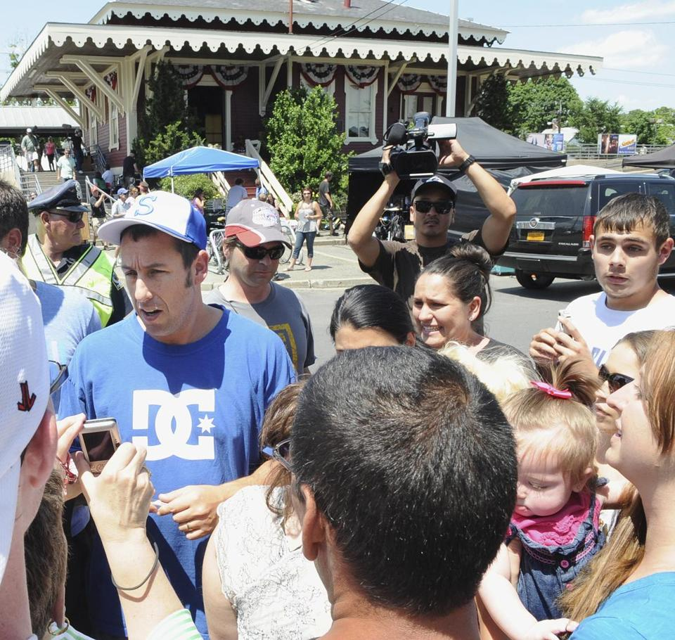 Actor Adam Sandler, left, greeted his fans between takes of the film, near the train station in Swampscott, Mass.