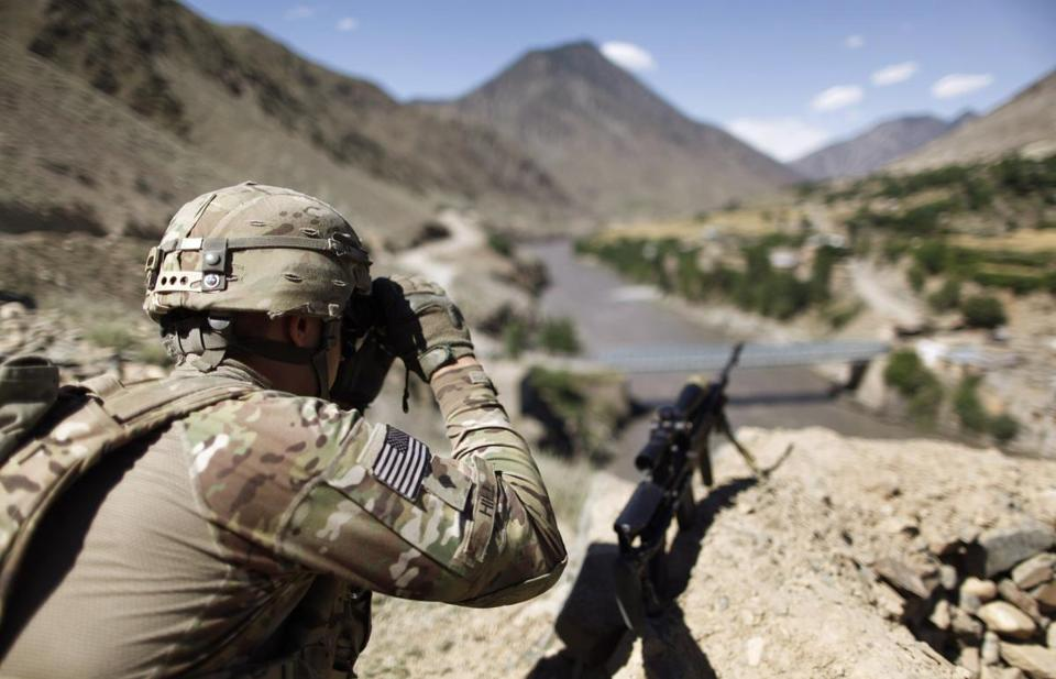 A soldier scans across the border at houses in Pakistan during a June patrol in Afghanistan.