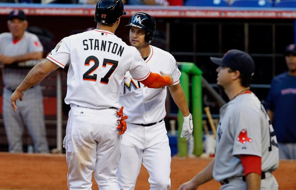 Miami's Giancarlo Stanton (27) is greeted by teammate Chris Coghlan after Stanton scored on a base hit by Gaby Sanchez in the first inning as Josh Beckett looks on.