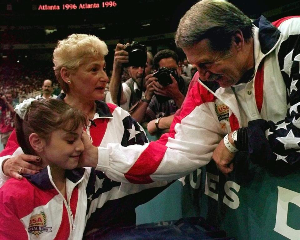 Dominique Moceanu with her coaches Marta and Bela Karolyi at the Olympics in 1996.