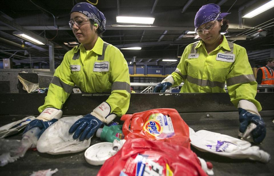 Plant workers help machines sort through materials at Casella Waste Systems' recycling center in Charlestown.