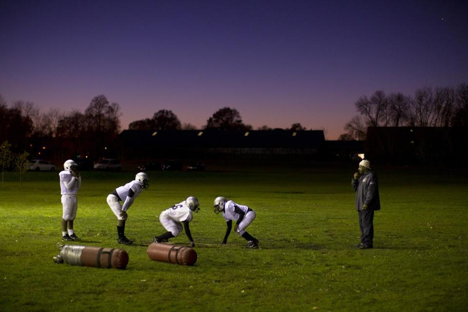 A Pop Warner coach led young athletes through drills on a November evening in 2010.