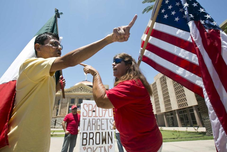 A man with a Mexican flag and a woman with an American one debated Arizona's immigration law at the State Capitol.