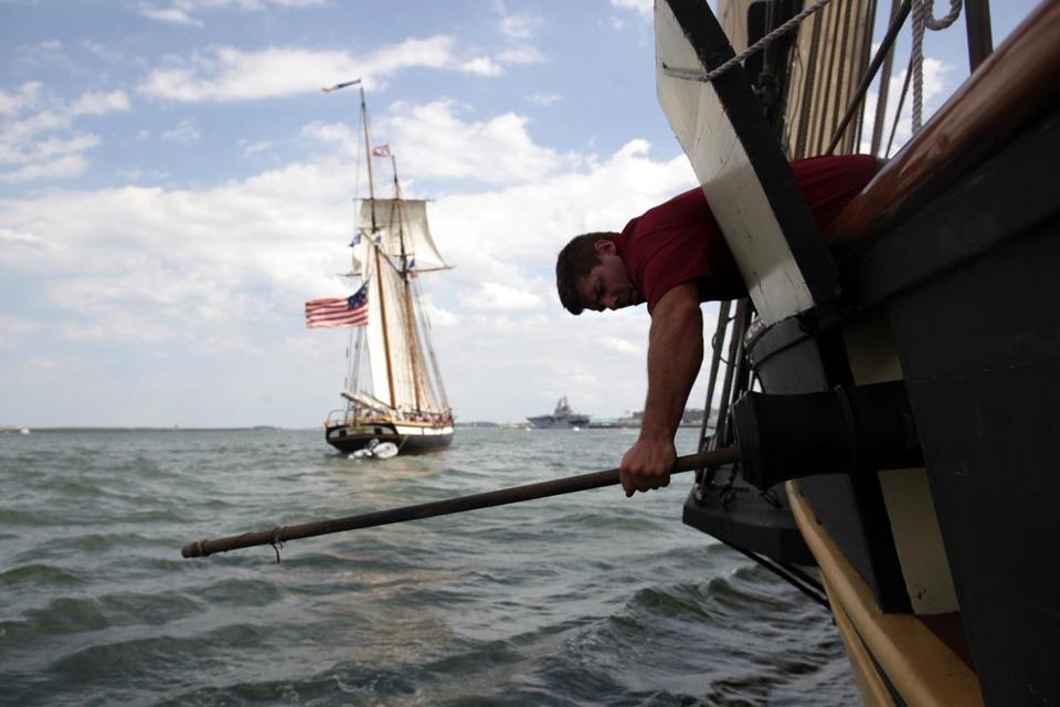 Second mate John Pickering cleaned the barrel of a replica smooth-bore gun aboard the Pride of Baltimore II during a battle reenactment against the Privateer Lynx on Sunday.