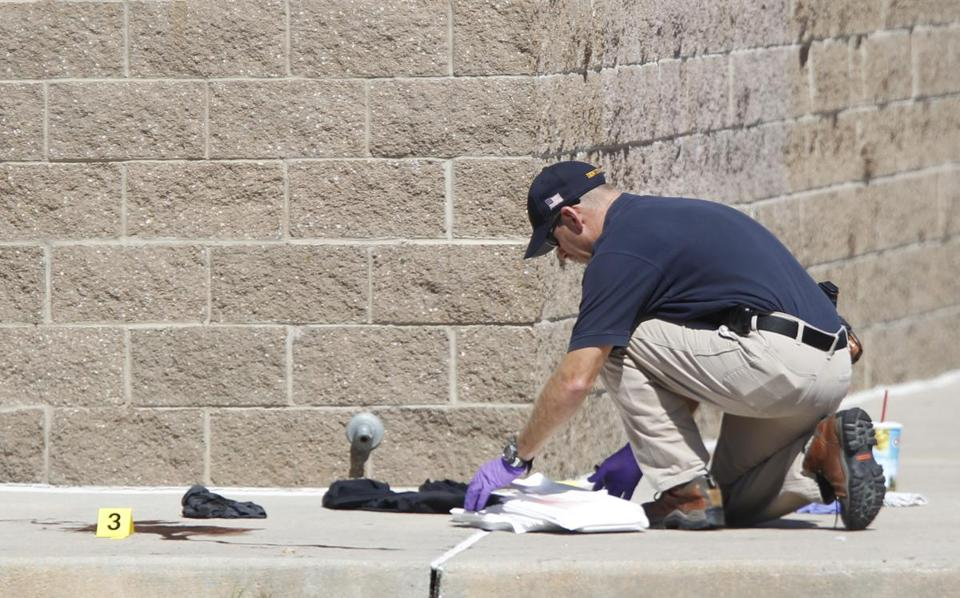 An investigator inspected evidence outside of a movie theater in Aurora, Colo., after a gunman killed at least 12 people.