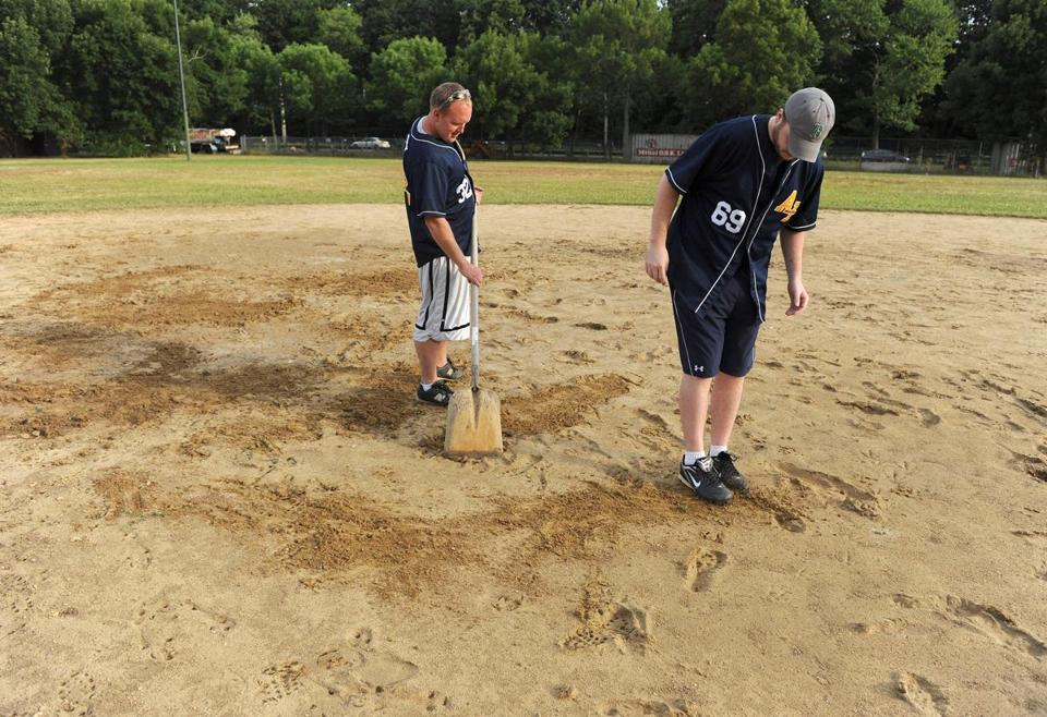 Scott Anderson (left) and Adam Vachon worked on leveling a part of Brighton's Daly Field last week. A bill is being discussed to limit the field's use at certain times to a few groups.
