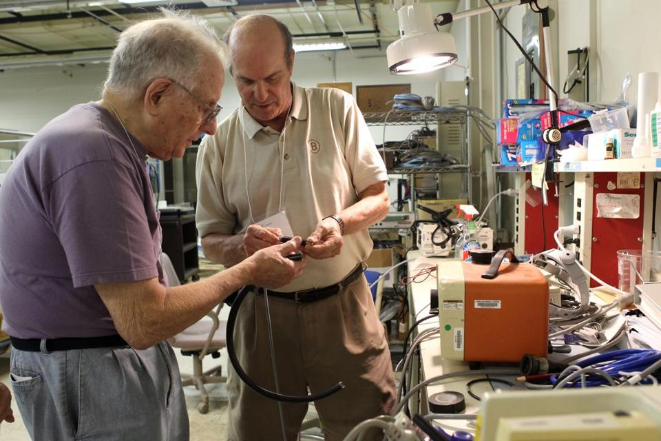 Fred Greenberg (left), a sound contractor, and Jay Gooze, an ophthalmologist, both of Durham, N.H., try to repair an optical unit so that it can be sent overseas.