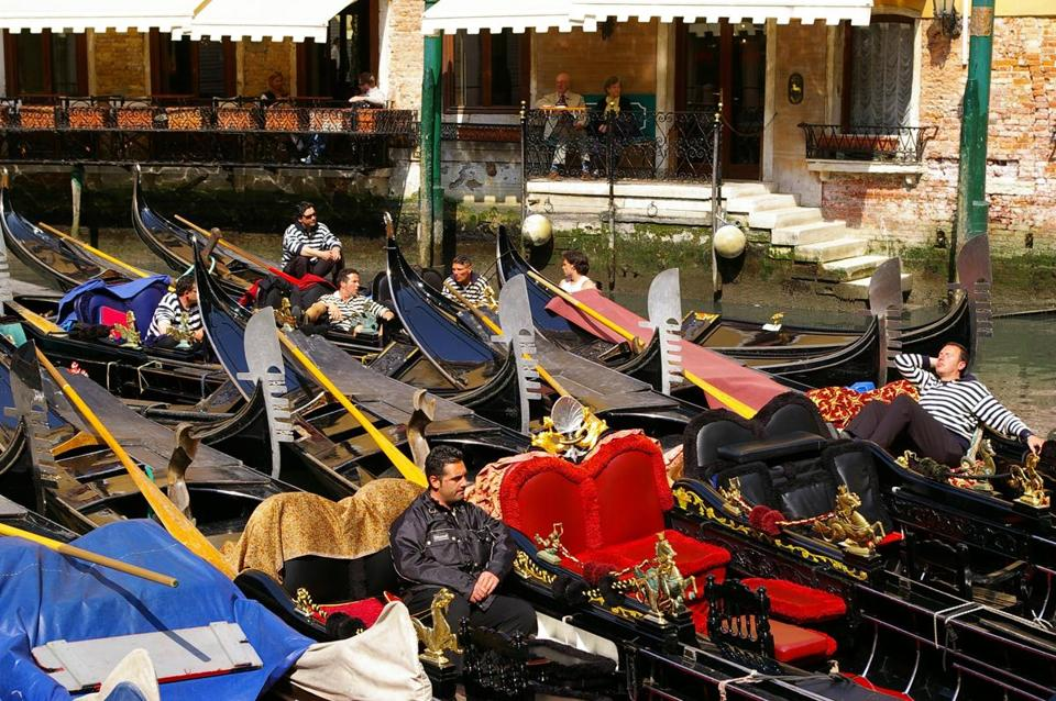 "When business is slow, the gondoliers in Venice relax in the sunshine on the back canal ""parking lot'' for the long, flat-bottomed boats."