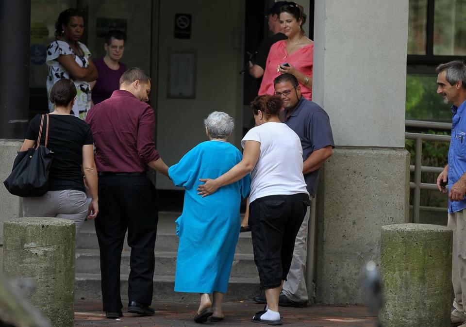 A resident was helped back into the Brighton apartment building where a woman was found dead Tuesday. Firefighters who responded to a fire in the building were attacked by a man residents said was the deceased woman's son.