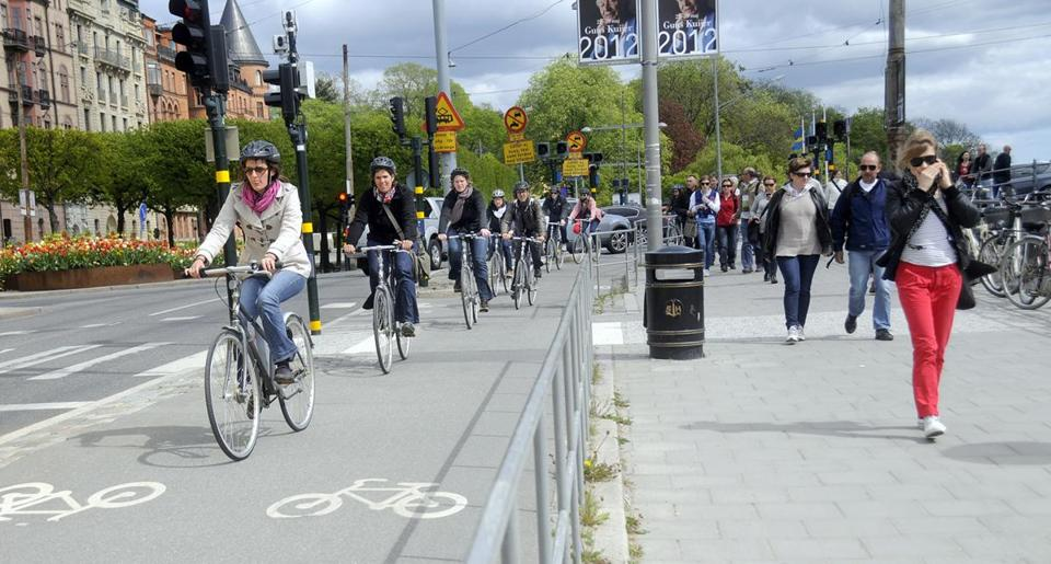 Bicyclists and pedestrians travel in Stockholm, where traffic has decreased significantly since the city started charging drivers a fee to enter congested areas.