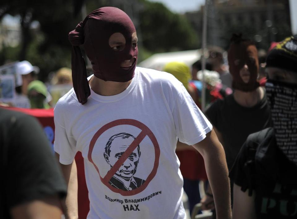 A supporter of the punk band wore a-shirt with the face of Russian President Vladimir Putin crossed out in red at a protest in Barcelona on Friday.