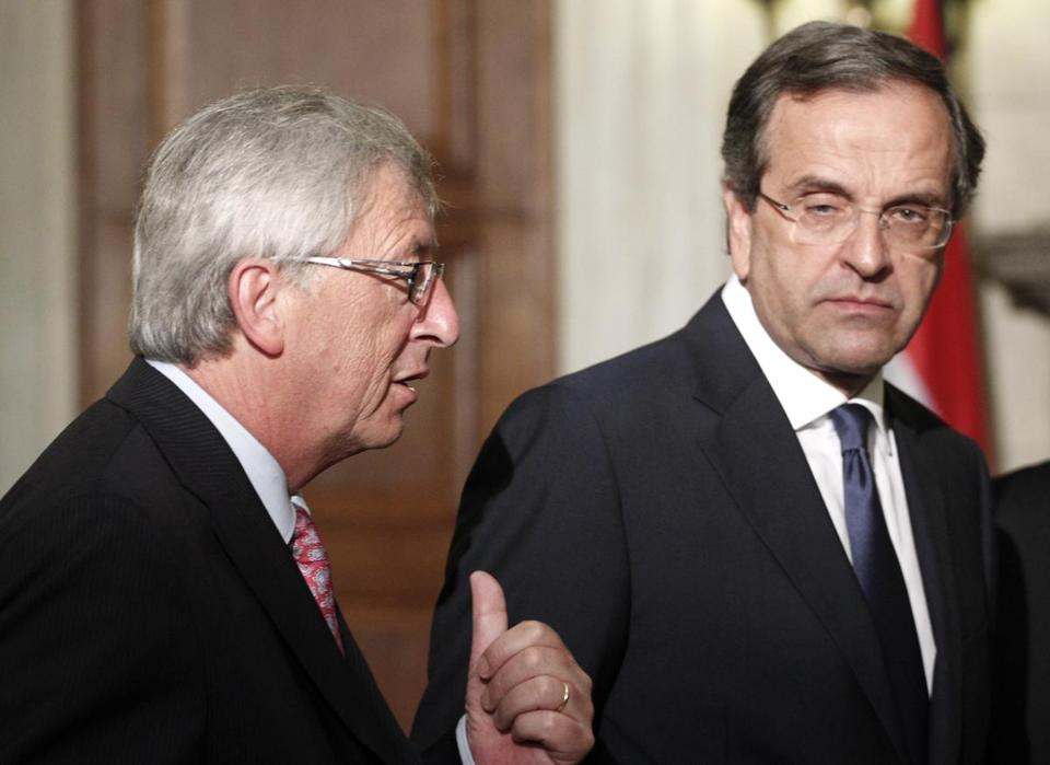 Greek Prime Minister Antonis Samaras, right, listened as Jean Claude Junker, prime minister of Luxembourg, spoke at a joint news conference after their meeting in Athens Wednesday