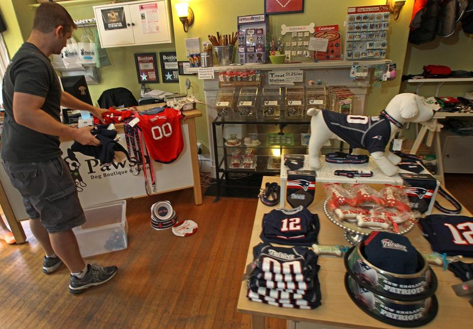 Mike Maida arranges Patriots items at Pawsh dog boutique in Back Bay. Only tourists have been buying Red Sox gear, he said.