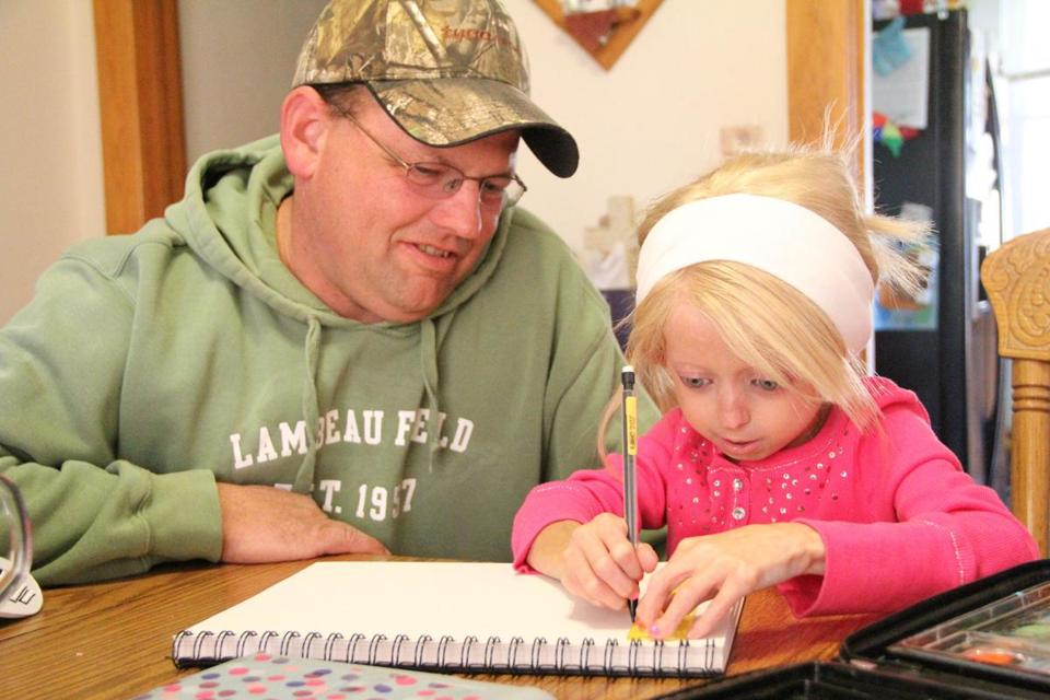 Steve Nighbor of Wisconsin helped his daughter Megan, 12, who has been diagnosed with progeria, with homework.