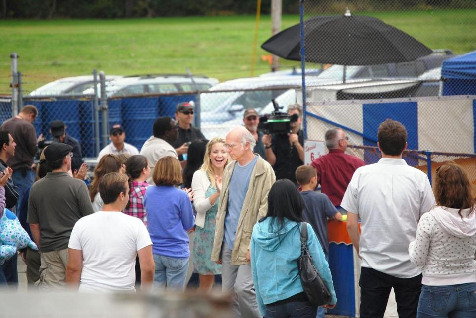 "At the center of a crowd, Kate Hudson cheers while Larry David grimaces during filming of ""Clear History"" on Oct. 2 at the Topsfield Fair."