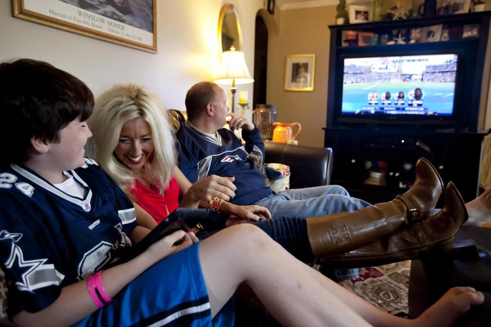 On a recent Sunday, Sean Kennedy watched NFL on TV, while Kimberly and Theo studied fantasy stats.