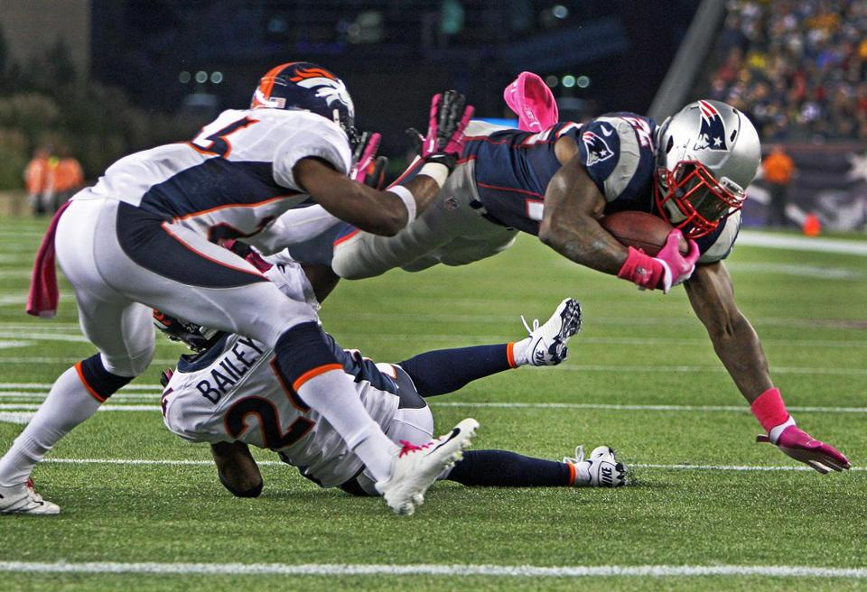 The Patriots' Stevan Ridley, who rushed for 151 yards in the game, sails over Denver cornerback Champ Bailey as he scores on an 8-yard run in the third quarter.