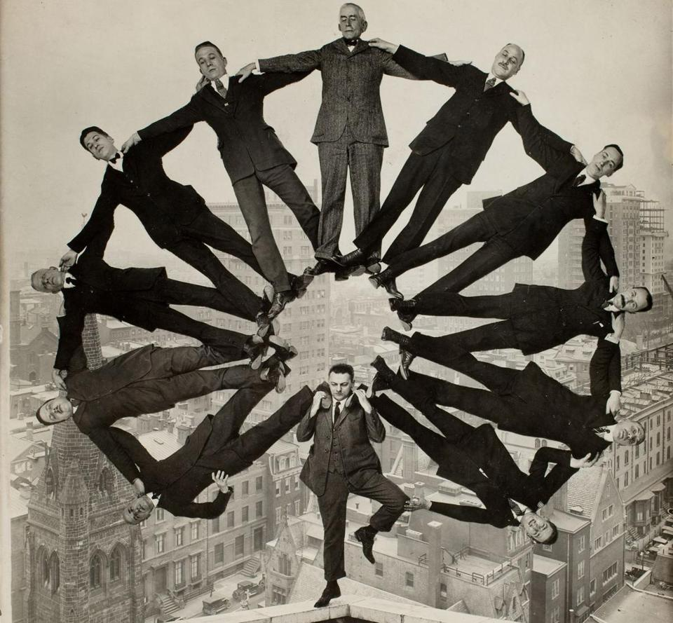 An unidentified artist's trick photo of a man holding up 11 men in formation, circa 1930.