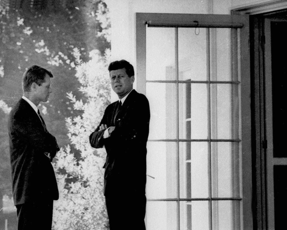 President Kennedy (right) confers with Robert F. Kennedy.
