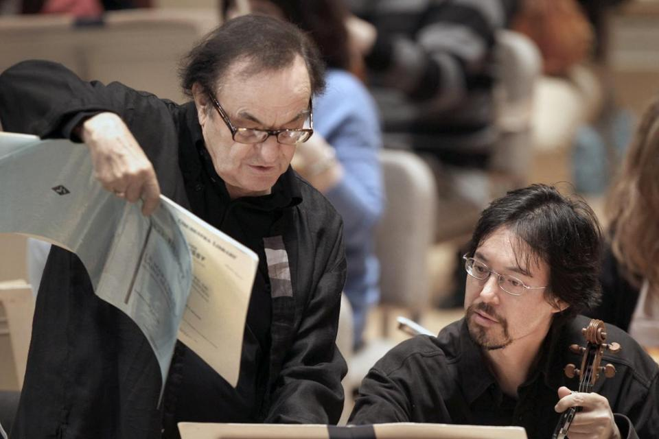 Conductor Charles Dutoit consults the score with Haldan Martinson, BSO principal second violin, at rehearsal last week.