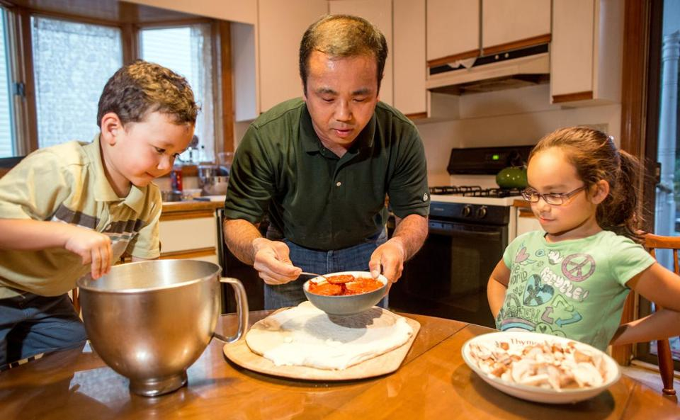 Fluto Shinzawa, who might otherwise have been on the road covering the Boston Bruins, instead makes pizza in Roslindale with his children, Wright, 3, and Hana, 6.