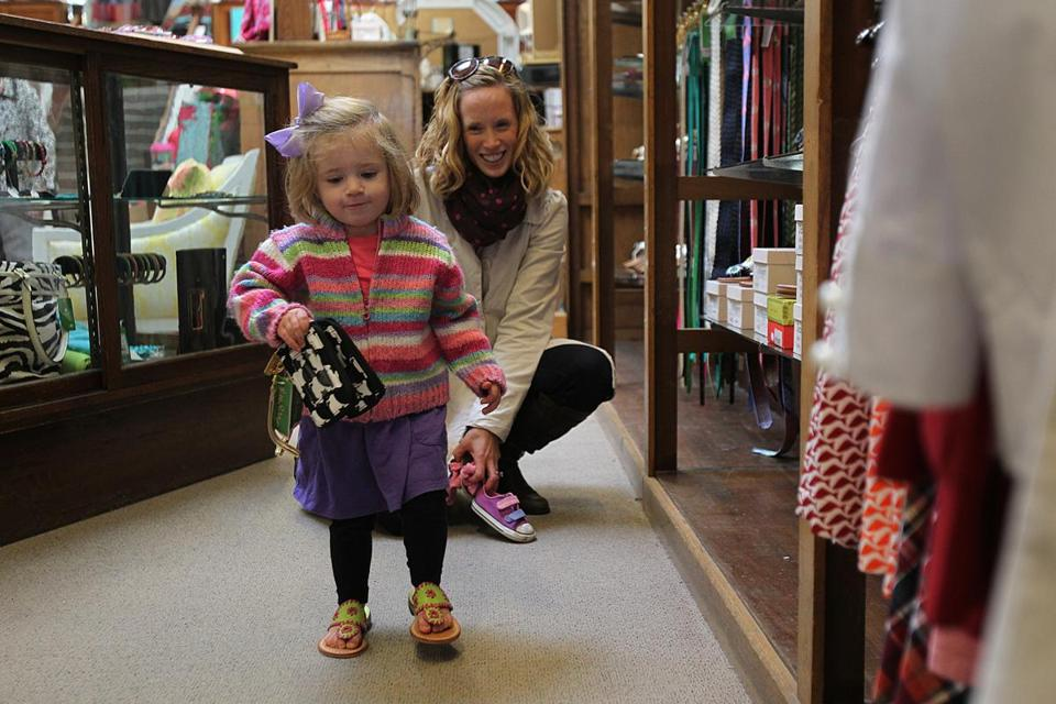 Generations have shopped at E.A. Davis in Wellesley, where Lily Magit, 2, tries out shoes and bags with her mother, Karen, and an old cash trolley runs along the ceiling, antiques are on display in the basement, and a 1912 brass cash register is kept on a counter.