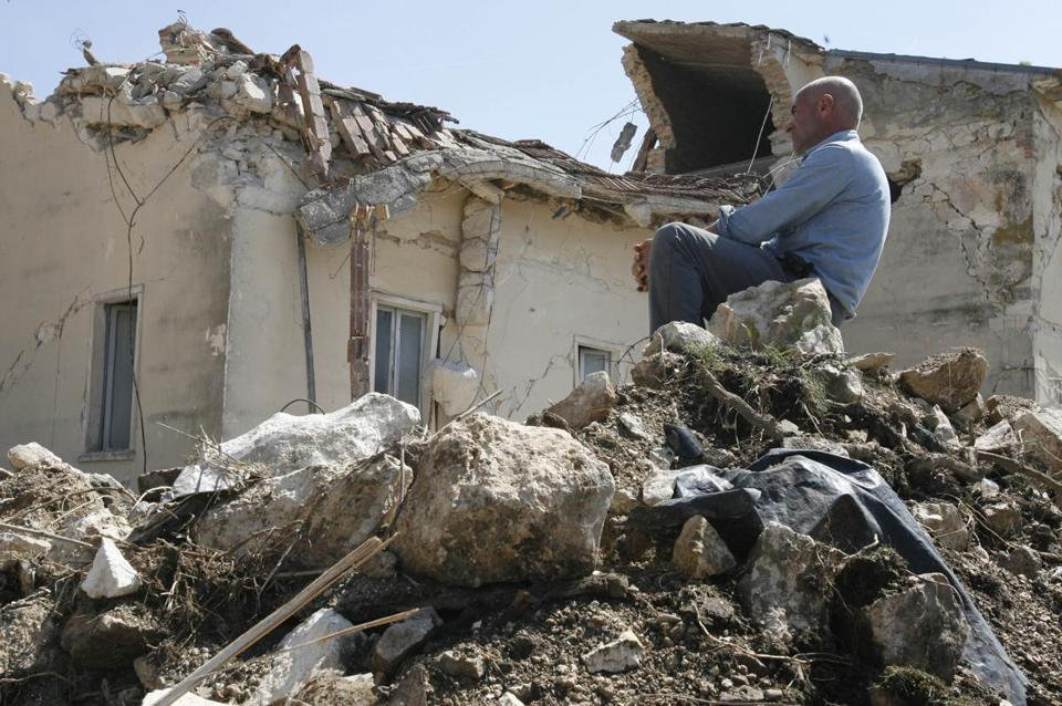 A man sat atop rubble in Onna in April 2009, after an earthquake struck the Abruzzo region in Italy. A court Monday convicted seven scientists in connection with the quake.
