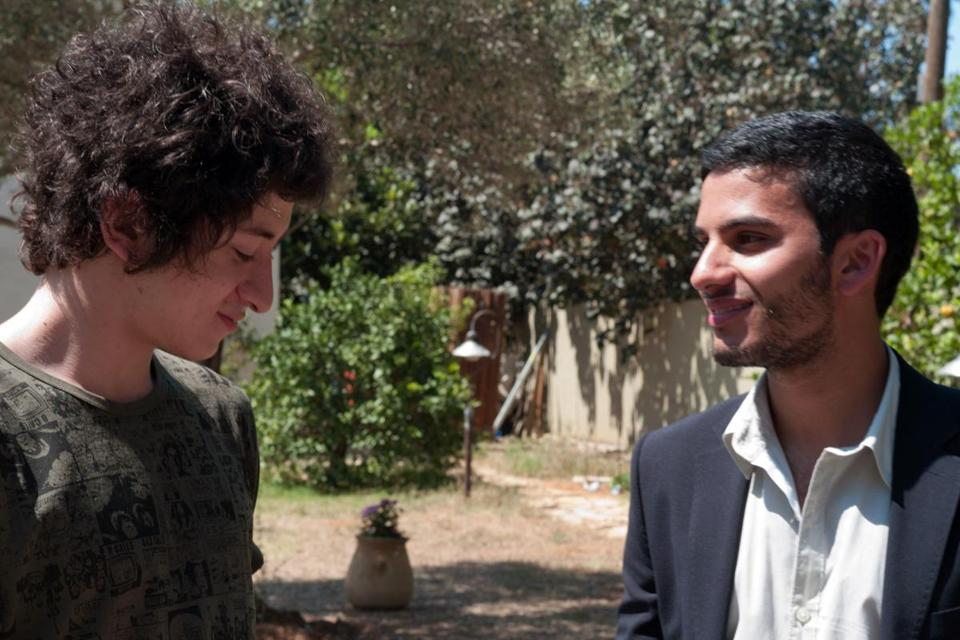 Jules Sitruk (left) and Mehdi Dehbi as young men switched at birth in their Israeli and Palestinian families.