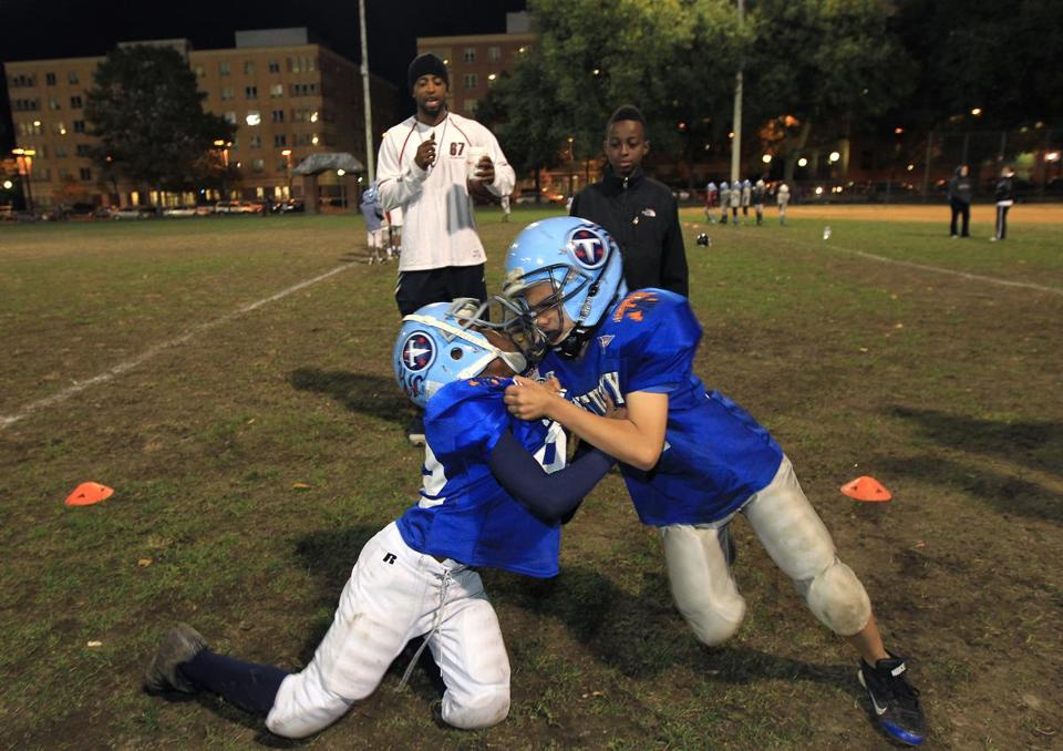 "Kieve Robinson, head coach of the South End/Roxbury Titans ""D"" team, oversaw tackling practice for Omarey Reddick, 9 (left), and Michael Deleon, 8."