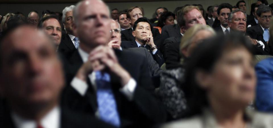 "Anh ""Joseph"" Cao, center, listens to President Obama speak before the signing the Dodd-Frank act in 2010."