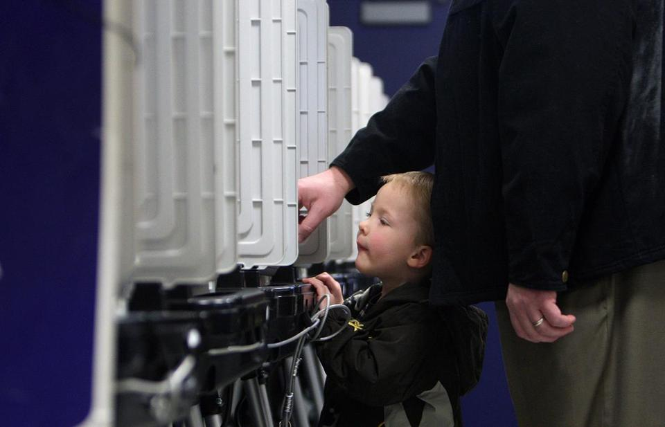 BradleyWilliams, 3, leans over to take a look as his dad, Doug, casts his vote during Super Tuesday in Sandy Springs, Ga., in March.