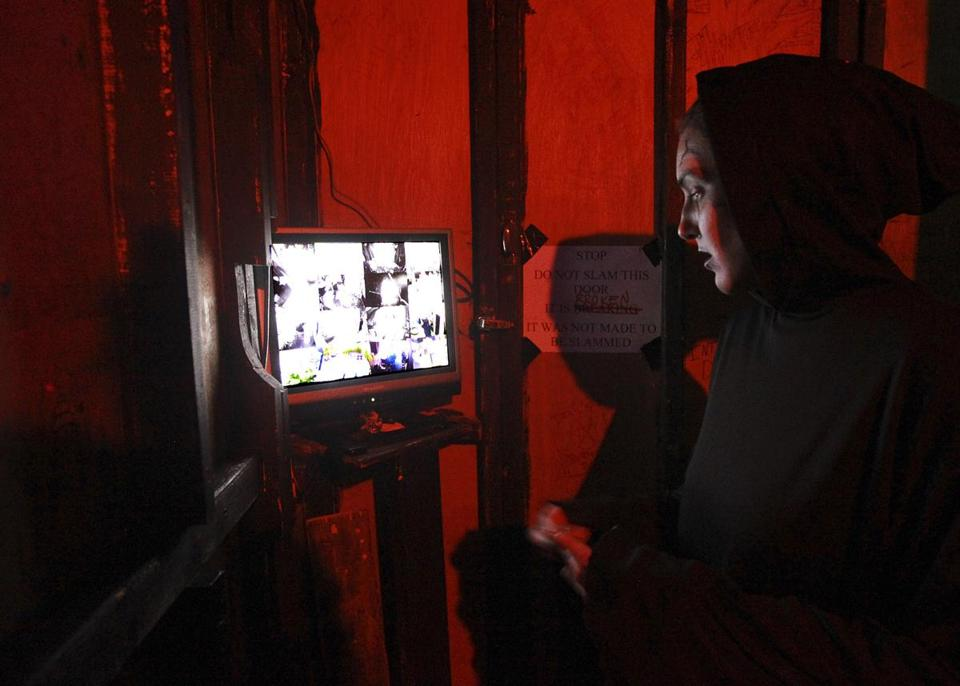 Actress Stephanie Perks monitored a video screen showing several views inside the Salem's 13 Ghosts haunted house. She waits for a cue to jump and try to scare visitors.