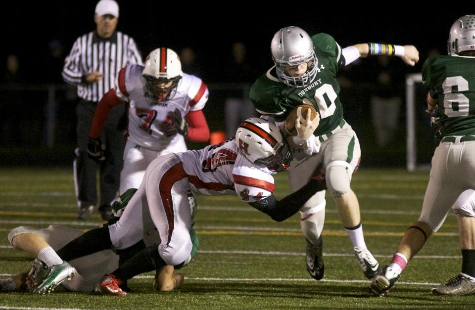Duxbury quarterback Sean McCarthy can't find any running room as Hingham's Josh Genovese closes off the lane in the second quarter.