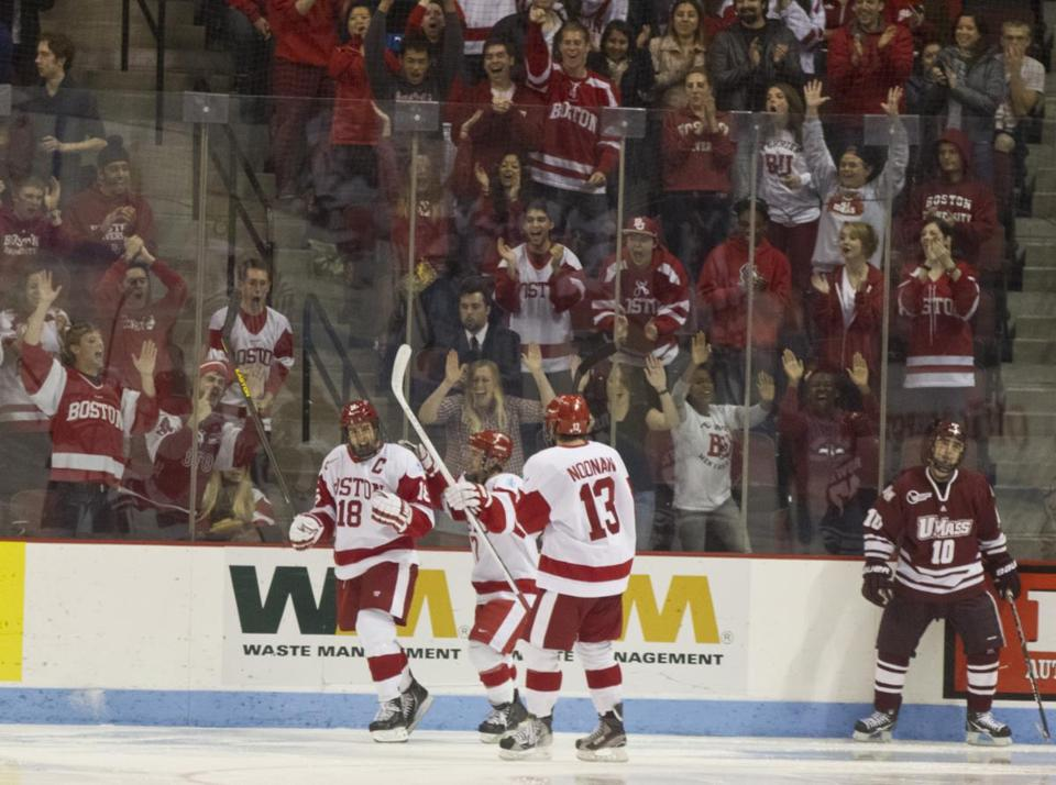 Wade Megan (18) got BU on the board in the second period — and its fans fired up — and celebrated with Cason Hohmann and Garrett Noonan.