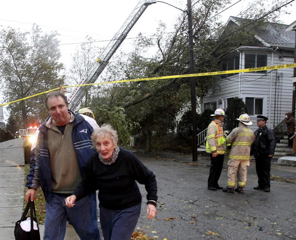 Joseph Reggio helped his mother, Rose, in Watertown on Monday after a tree collapsed on her apartment building.