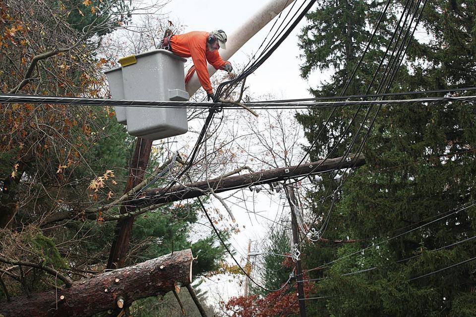 A Needham public works employee clears broken branches from downed lines at South and Chestnut streets in the storm's wake Tuesday.