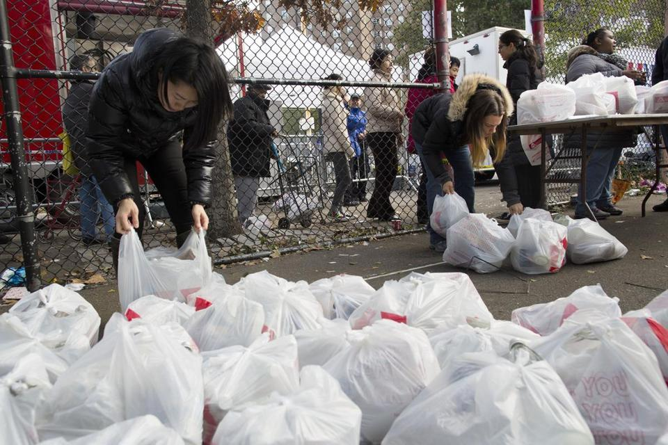 People lined up behind a fence for distribution of food, water, and other supplies in Manhattan on Friday.