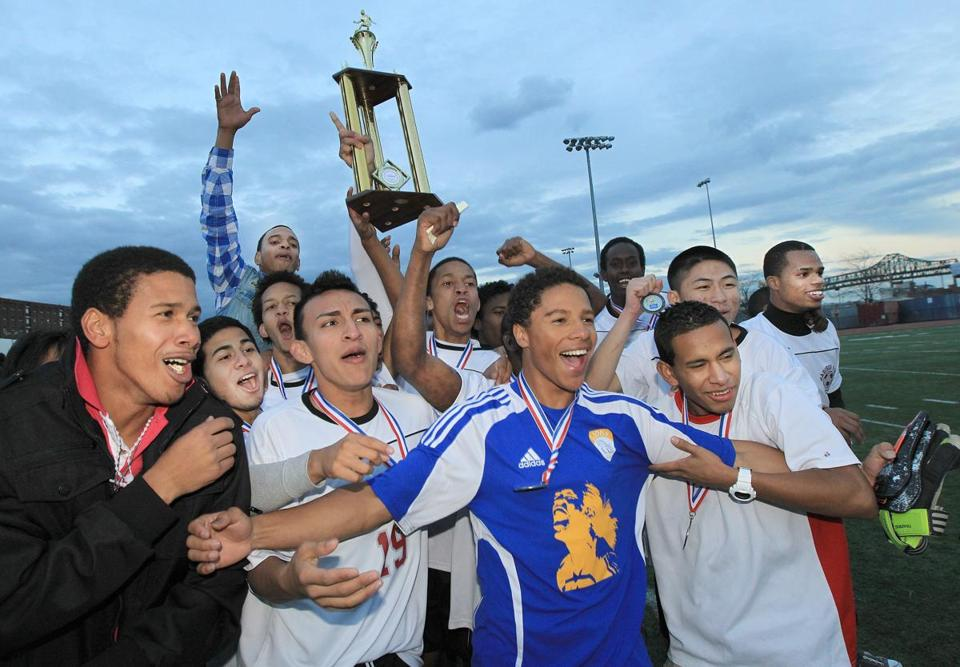 Madison Park's soccer team hoists the trophy high after defeating Boston International in a shootout for the Boston City League title.