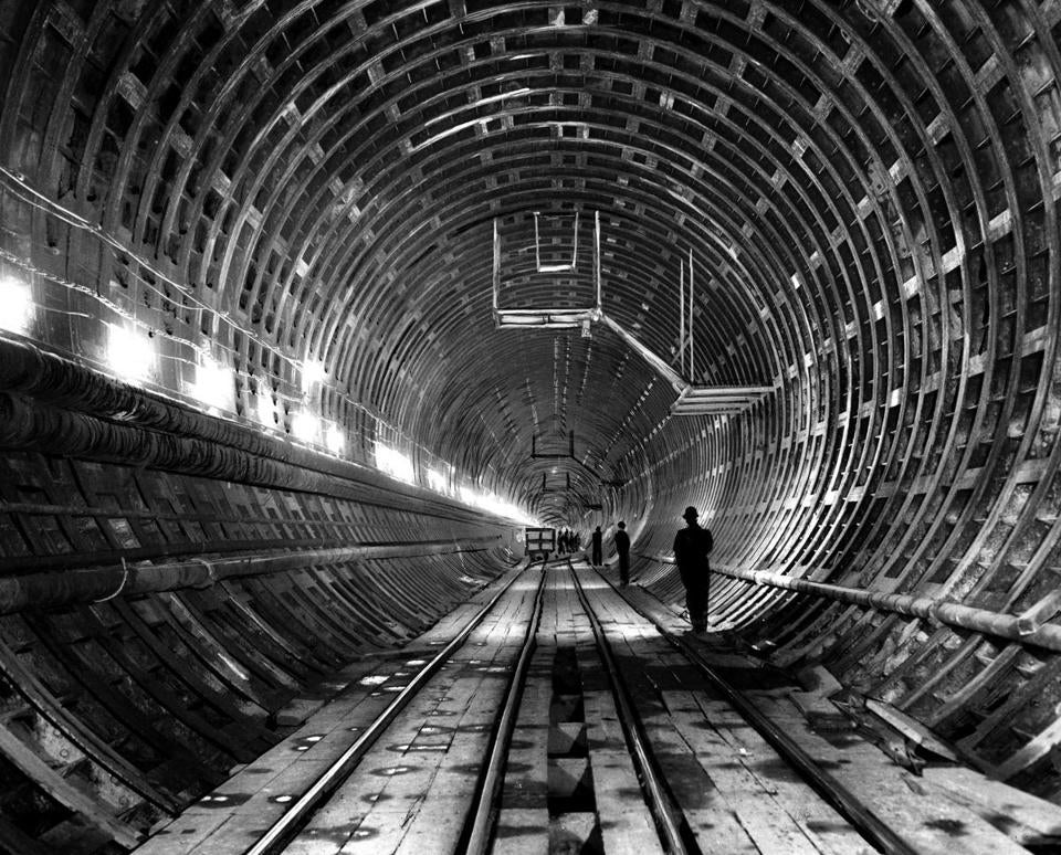 "March 23, 1961: The steel ribs of the Lieutenant William F. Callahan Jr. tunnel stretch as far as the eye can see under Boston Harbor from East Boston to Boston. The 14,500 tons of special structural steel used to fabricate the basic lining of the tube came via rail to East Boston from Youngstown, Ohio. The massive corrugated series of curved steel plates when bolted together form ""rings."" In the case of the new tunnel, concrete forms the secondary lining inside the rings. A total of 1,813 rings, each composed of 11 segments, are locked tightly into place."