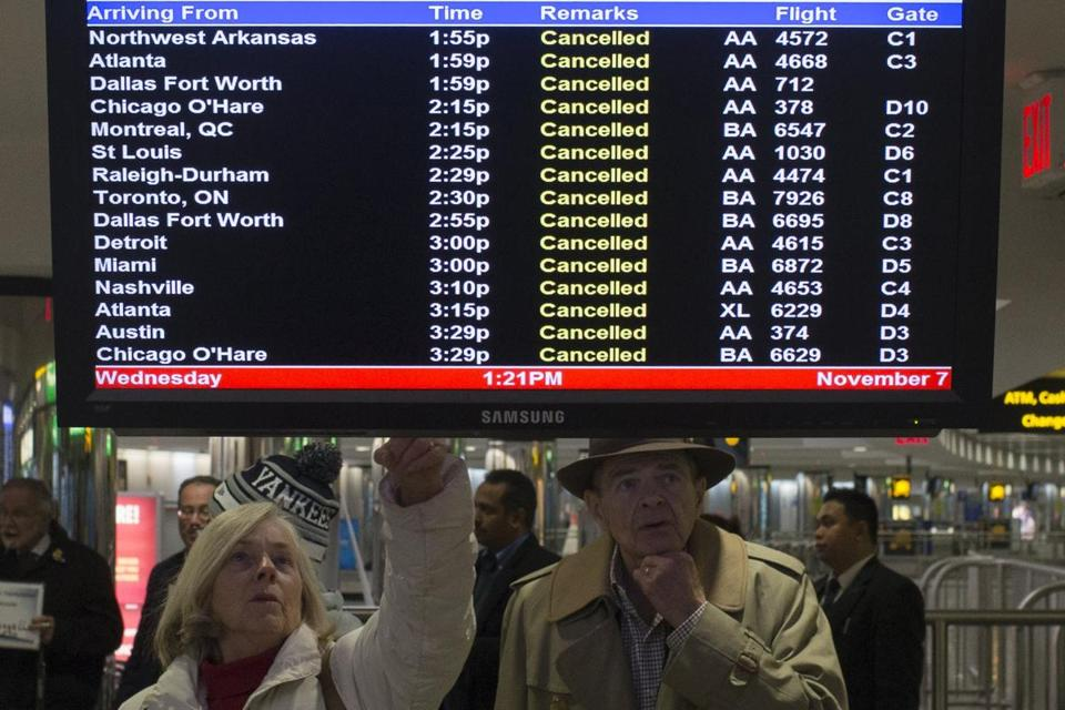 Travelers looked over a list of canceled flights in New York's LaGuardia Airport.
