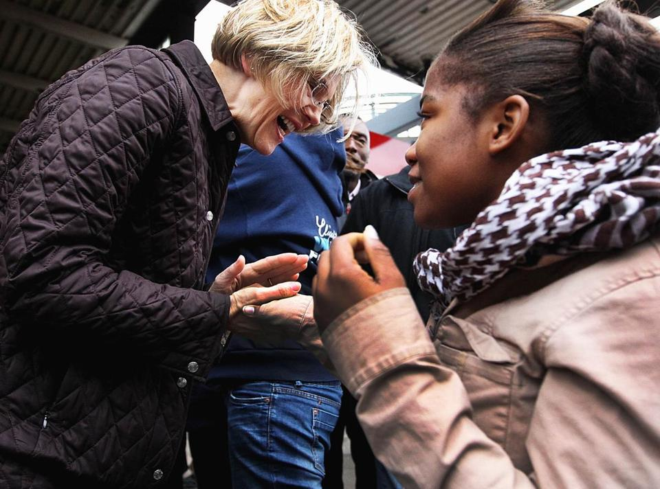 Elizabeth Warren greeted a young supporter at Broadway MBTA stop in South Boston Wednesday.