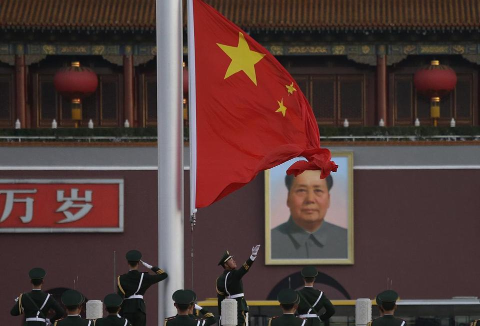 "Paramilitary policemen saluted while a Chinese national flag was raised at Tiananmen Square with Chinese characters that read ""Long Live"" beside a portrait of Mao Zedong."