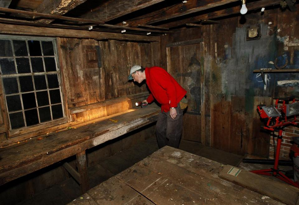 Preservation specialist Michael Burrey looks around an 18th century craftsman's shop recently discovered on the grounds of the Berrybrook School in Duxbury.