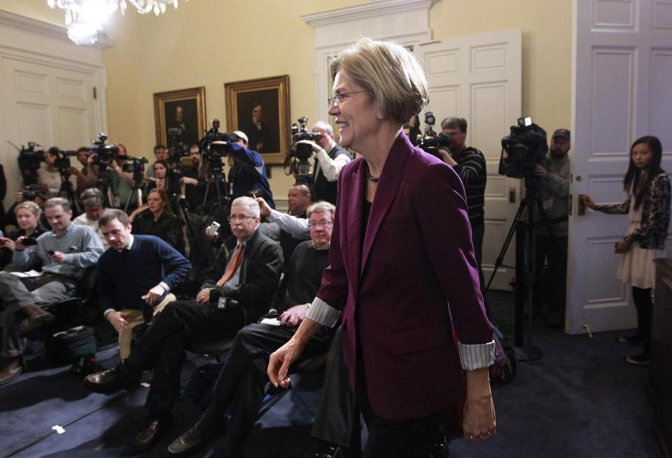 US Senator-elect Elizabeth Warren walked past members of the media Wednesday as she made her way to the podium at the State House for her first post-election news conference.