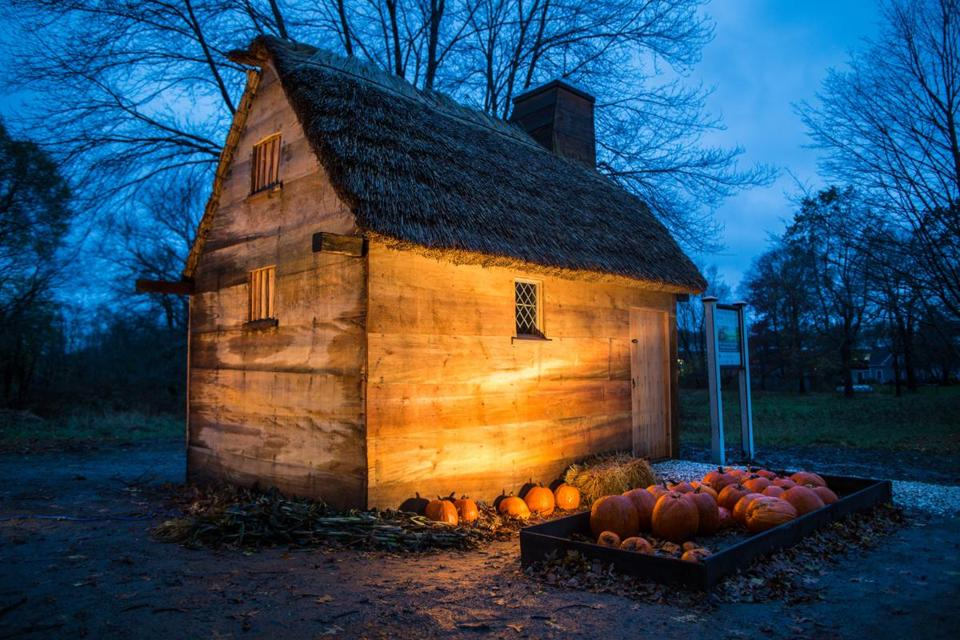 A recreation of the 1657 Alexander Knight House is illuminated at dusk.