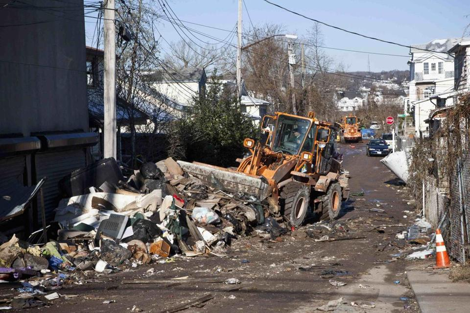 Sanitation workers cleared garbage from a street on Friday in the Midland Park section of Staten Island.