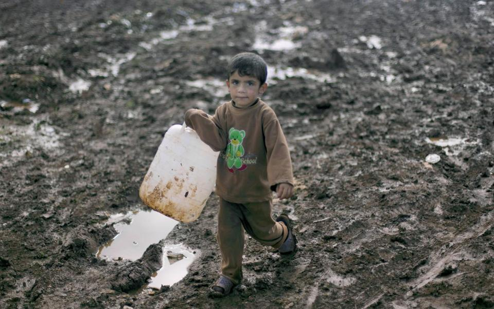 A boy fetched water at a refugee camp in the village of Atma in Syria. Thousands have been displaced since 2011.