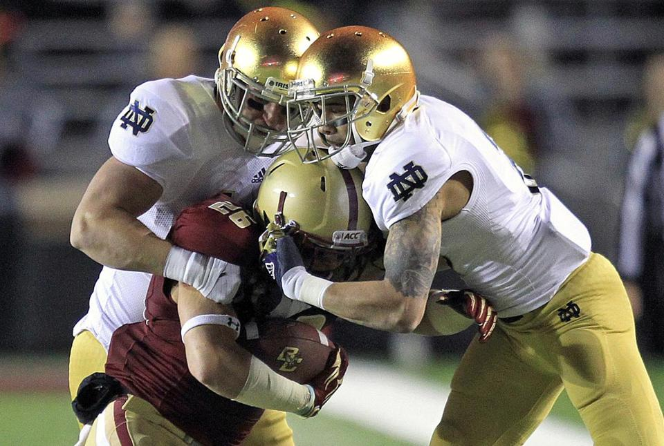 BC freshman running back David Dudeck gets stacked up by a pair of Irish defenders.