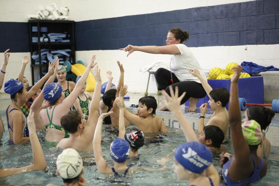 Coach Kristen Powers (center) instructed team members during water polo practice at the Charles River YMCA in Needham.