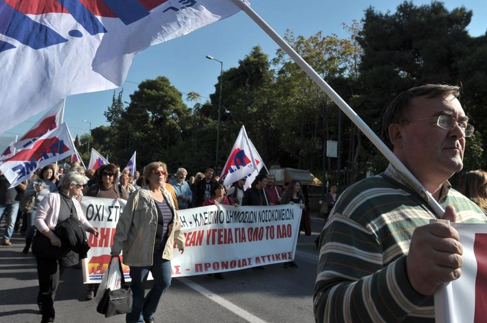 Public-sector employees protested expected layoffs on Tuesday in central Athens. The sale of short-term treasury bills may avert some woes: The $5 billion raised will help Greece make a crucial debt repayment by the end of the week.